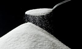 Sugar falling from Silver Spoon. Focus on edge of spoon sugar pile top.
