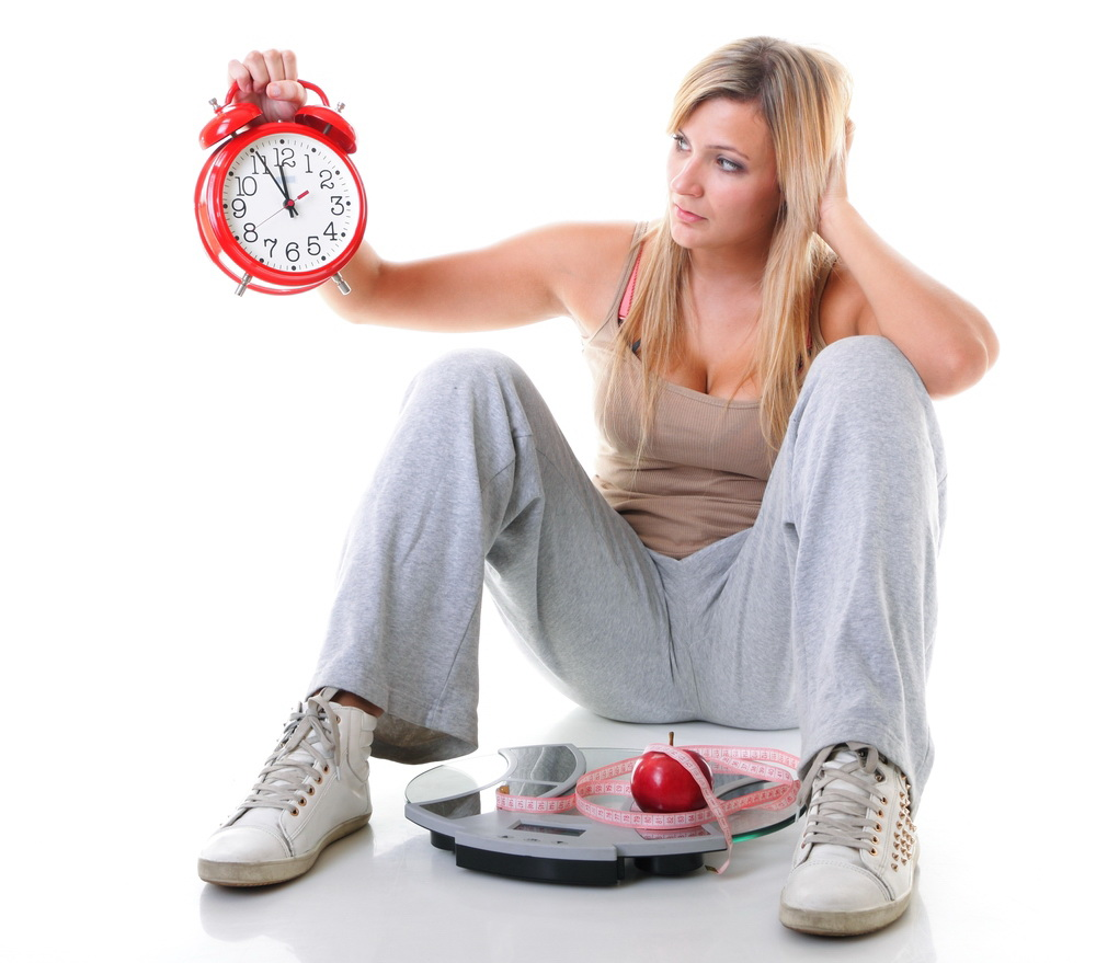 Time for diet slimming. Woman plus size large girl with clock scales apple measuring tape - weight loss concept. Isolated on a white background.
