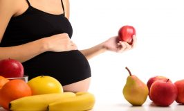 Healthy nutrition and pregnancy. Pregnant woman and red apple, isolated white background