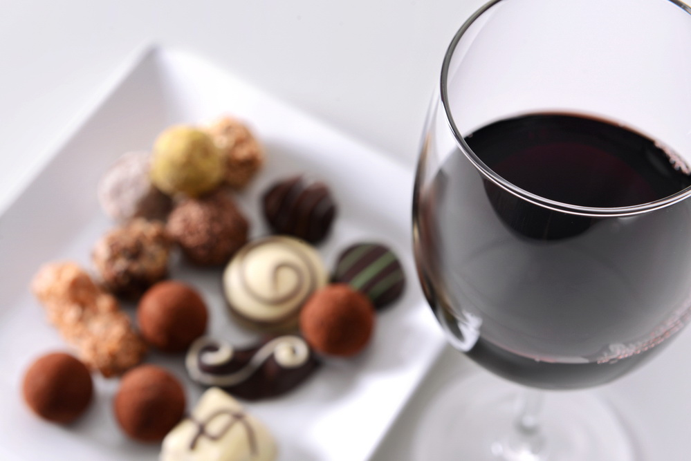 Glass of red wine and delicious chocolate candies on white background