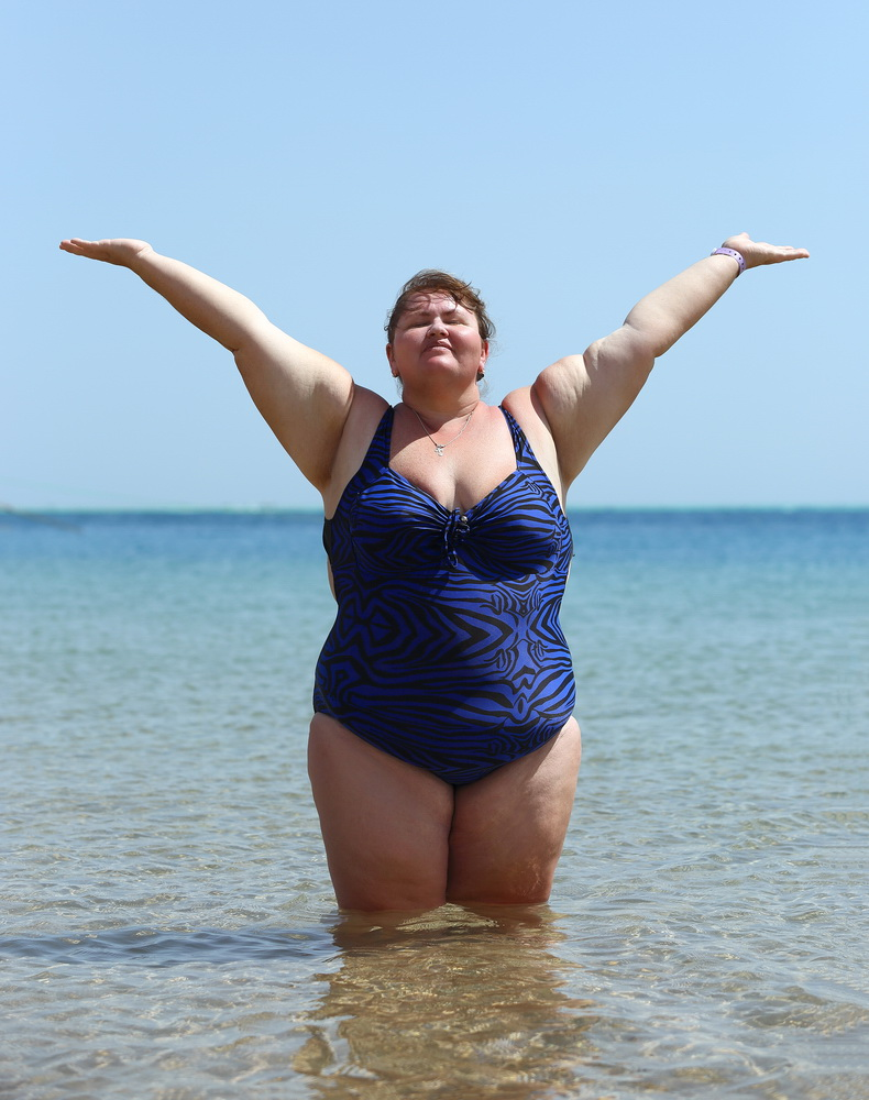 overweight woman standing in sea on beach with hands up
