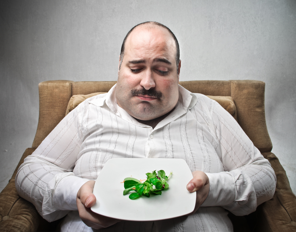 Sad fat man looking at his dish containing barely salad
