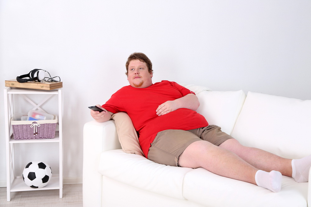 Lazy overweight male sitting on couch and watching television